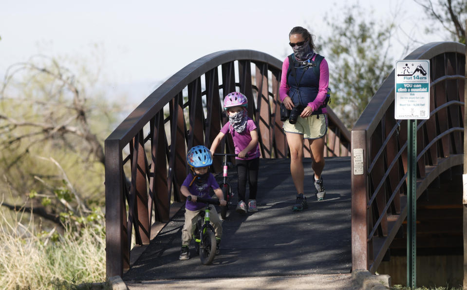 A woman and children wear face coverings as a precaution against the coronavirus while crossing a bridge in Barr Lake State Park Sunday, May 17, 2020, near Brighton, Colo. (AP Photo/David Zalubowski)