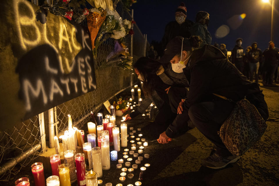 A woman lights a candle as people gather for Kevin Peterson Jr., who was killed in Thursday's shooting with police involved, at a candlelight vigil in Vancouver, Wash., Friday, Oct. 30, 2020. The Clark County Sheriff's office has not released any details on the Thursday evening shooting in Hazel Dell, but a man told The Oregonian/OregonLive that his 21-year-old son was fatally shot by police. (AP Photo/Paula Bronstein)