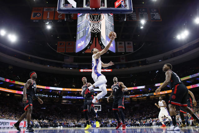 Philadelphia 76ers' Ben Simmons, center, goes up for a shot past Toronto Raptors' Terence Davis, from left, Rondae Hollis-Jefferson, Serge Ibaka and Kyle Lowry during the first half of an NBA basketball game, Sunday, Dec. 8, 2019, in Philadelphia. (AP Photo/Matt Slocum)