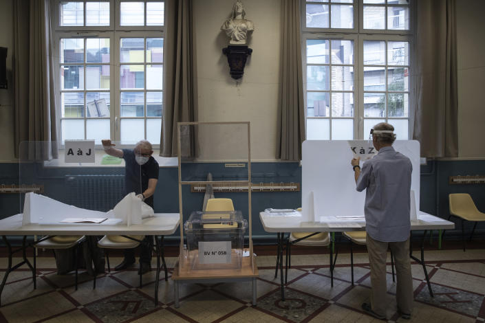 People install plexiglass as part of security measures in a polling station for the second round of the municipal elections, Sunday, June 28, 2020 in Paris. France is holding the second round of municipal elections in 5,000 towns and cities Sunday that got postponed due to the country's coronavirus outbreak. (Joel Saget, Pool via AP)