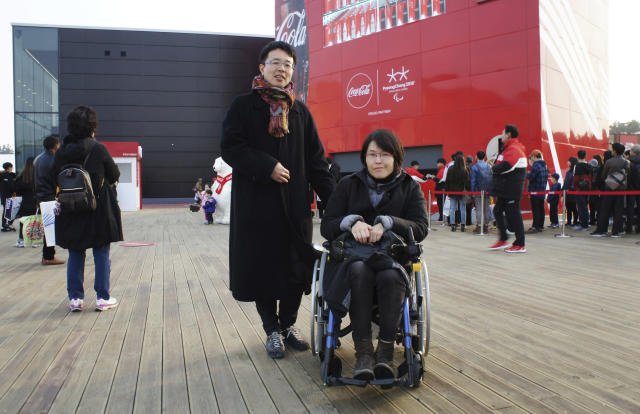 In this March 12, 2018, photo, Japan's Tomoko Inujima, right, poses with her husband Yoshihiro Nakabo near the Gangneung Hockey Center in Gangneung, South Korea. Inujima, a wheelchair user from Tokyo who came to the games with her husband, said she ran into trouble entering restaurants and stores. However, she said the help from volunteer workers and local residents, who she found attentive and supportive, more than made up for it. (AP Photo/Kim Tong-hyung)