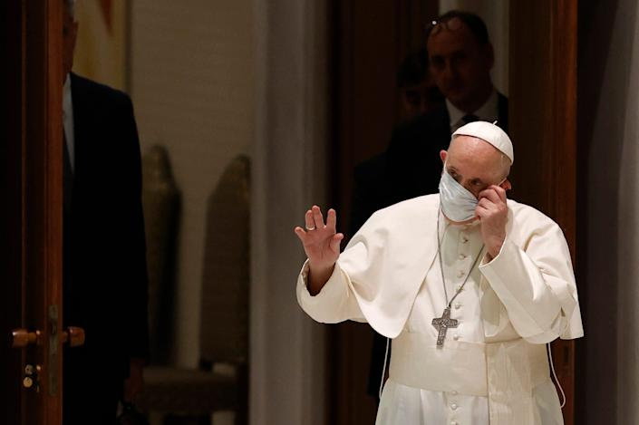 Pope Francis takes off his protective mask as he arrives to attend his weekly general audience in the Paul VI hall at the Vatican, Wednesday, Aug. 4, 2021.