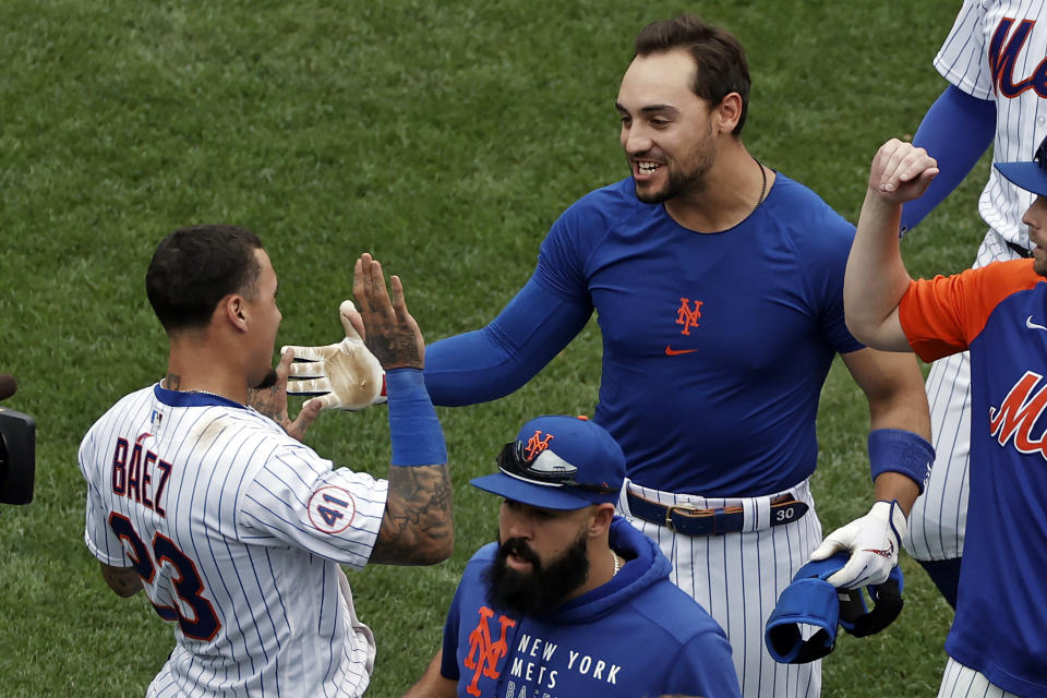 New York Mets' Michael Conforto celebrates with Javier Baez after defeating the Miami Marlins in the first game of a baseball doubleheader that started April 11 and was suspended because of rain, Tuesday, Aug. 31, 2021, in New York. The Mets won 6-5. (AP Photo/Adam Hunger)