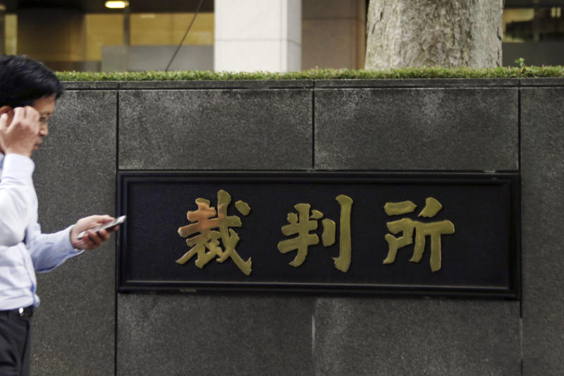 """FILE - In this June 26, 2017, file photo, a man passes by the Tokyo District Court in Tokyo. A worker at the major Japanese sportswear maker Asics said he is suing the company to counter the idea that a man's place is at work and a woman's is in the home. The father of two appeared at a hearing Thursday in the court, which is handling the case on """"pata-hara,"""" or paternity harassment. (AP Photo/Koji Sasahara, File)"""