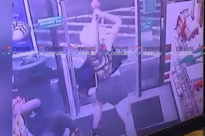 The blonde haired woman can be seen swinging the axe a third time as both injured customers try and protect their faces. Source: News Corp