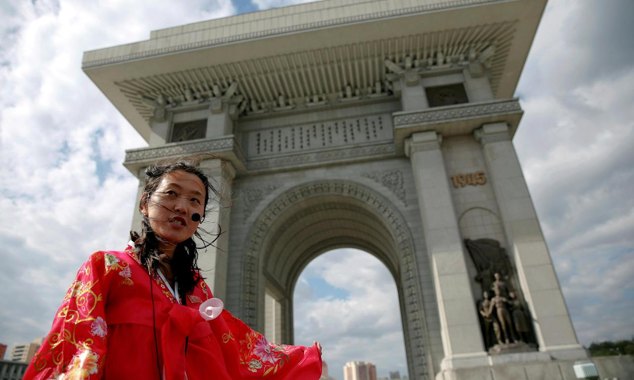 A guide wearing a traditional dress speaks to visitors at the Arch of Triumph in Pyongyang.