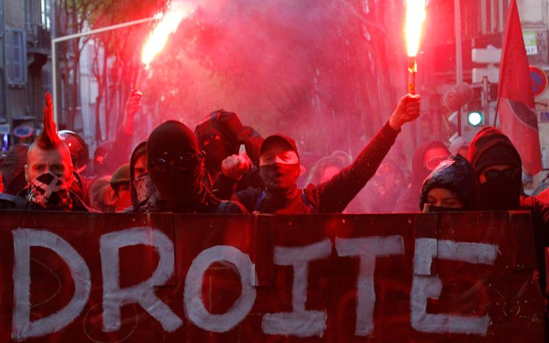 Masked youths behind a banner hold flares aloft - Credit: Philippe Laurenson/Reuters