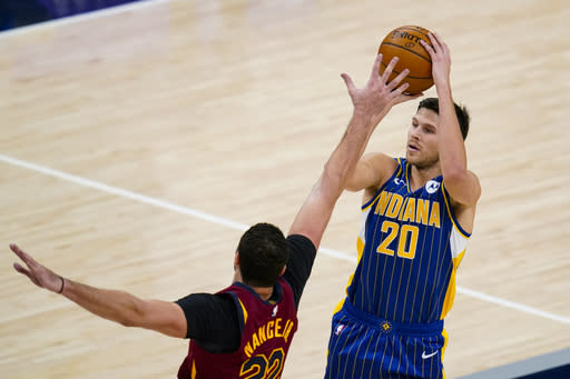 Indiana Pacers forward Doug McDermott (20) is fouled on a three-point shot by Cleveland Cavaliers forward Larry Nance Jr. (22) during the first half of an NBA basketball game in Indianapolis, Thursday, Dec. 31, 2020. (AP Photo/Michael Conroy)