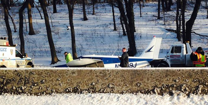 In this photo provided by Patricia Sapol, emergency personnel respond to a light airplane that made an emergency landing on the Major Deegan Expressway in the Bronx borough of New York, Saturday, Jan. 4, 2014. The Piper PA-28, set down at around 3:20 p.m. on the northbound side of the highway. Police and fire officials said neither the male pilot nor two female passengers appeared to have been badly hurt. (AP Photo/Patricia Sapol)