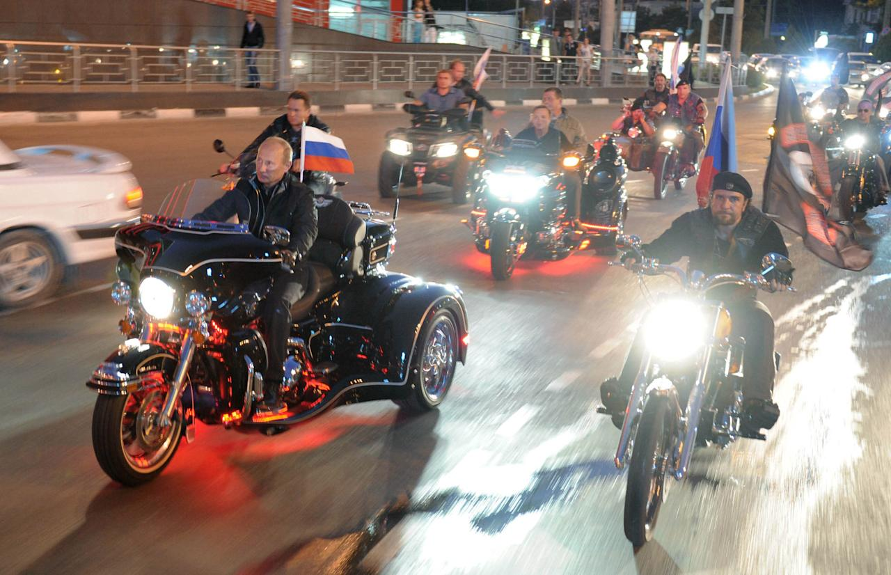 In this Monday, Aug. 29, 2011 photo, then Russian Prime Minister Vladimir Putin, center left, and leader of Nochniye Volki (the Night Wolves) biker group, Alexander Zaldostanov, also known as Khirurg (the Surgeon), right, ride bikes at a motor bikers' festival in the Black Sea port of Novorossiysk, Russia. Putin has become alternately notorious and beloved for an array of adventurous stunts, including posing with a tiger cub and riding a horse bare-chested. (AP Photo/RIA Novosti, Alexei Druzhinin, POOL, file)