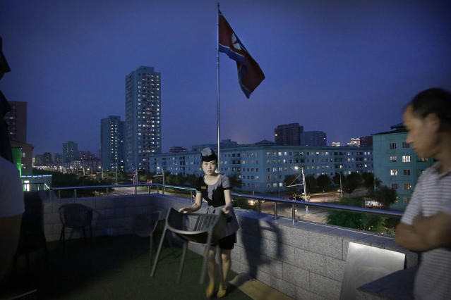 <p>A waitress moves a dining chair at a restaurant terrace that overlooks a residential street at dusk in Pyongyang, North Korea, June 19, 2017. (Photo: Wong Maye-E/AP) </p>