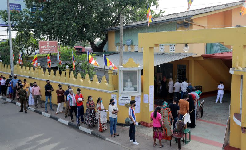 People wearing protective masks wait in a line outside a polling station as they prepare to cast their vote during the country's parliamentary election in Colombo