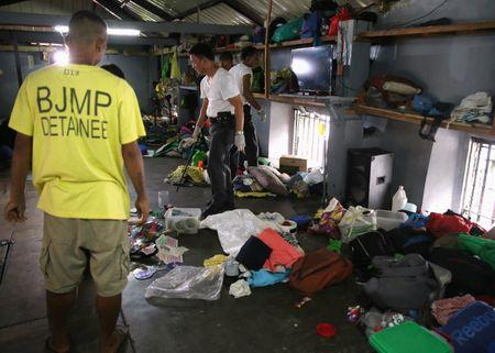 A detainee looks over authorities searching through their belongings for illegal contraband inside the Manila City Jail in metro Manila, Philippines October 16, 2017. REUTERS/Romeo Ranoco