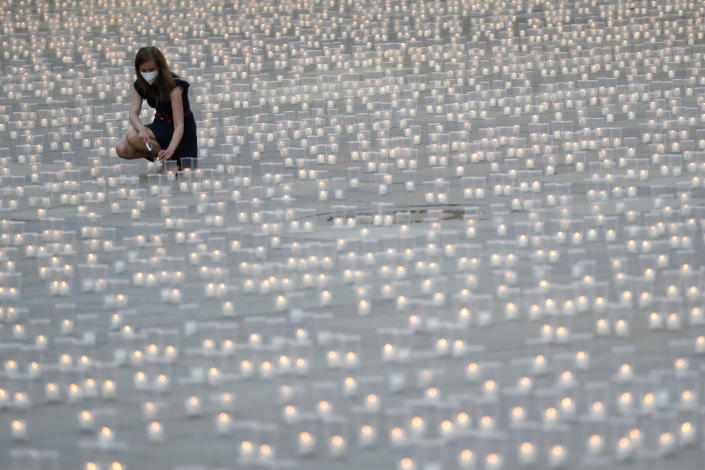 Woman lights a candle to commemorate victims of the COVD-19 pandemic at the Prague Castle in Prague, Czech Republic, Monday, May 10, 2021. The Czech Republic is massively relaxing its coronavirus restrictions as the hard-hit nation pays respect to nearly 30,000 dead. (AP Photo/Petr David Josek)