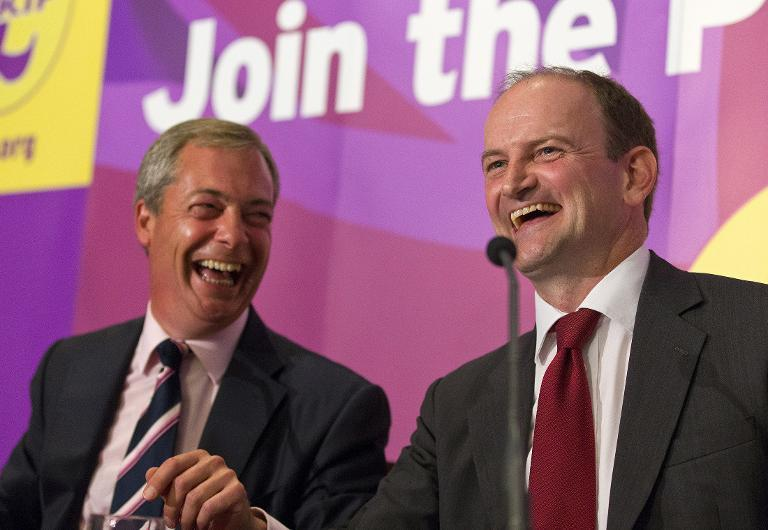 Defecting Conservative MP Douglas Carswell (R) addresses a press conference in central London on August 28, 2014, with UKIP leader Nigel Farage (L)