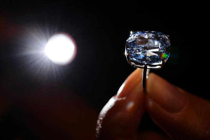 "Hong Kong property tycoon Joseph Lau has snapped up the 12.03-carat blue diamond dubbed ""Blue Moon"" for a record $48.4 million at Sotheby's in Geneva (AFP Photo/Fabrice Coffrini)"