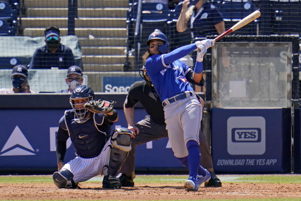Toronto Blue Jays' Bo Bichette, right, watches his solo home run off New York Yankees pitcher Luis Cessa during the fifth inning of a spring training exhibition baseball game in Tampa, Fla., Wednesday, March 24, 2021. It was Bichettes' second home run of the game. Catching is New York Yankees' Gary Sanchez. (AP Photo/Gene J. Puskar)