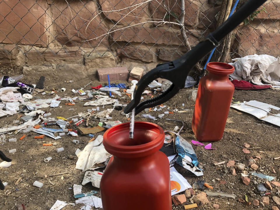 """FILE - In this Aug. 9, 2019, file photo, a drug syringe found behind a vacant property in northeast Albuquerque, N.M., is placed into a container, as crews attempt to clear the lot of needles and other heroin paraphernalia. In what would be a first in the U.S., possession of small amounts of heroin, cocaine, LSD and other hard drugs would be decriminalized in Oregon under a ballot measure that voters are deciding on in Tuesday's election. Instead of going to trial and facing possible jail time, a person would have the option of paying a $100 fine or attend new """"addiction recovery centers."""" (AP Photo/Mary Hudetz, File)"""