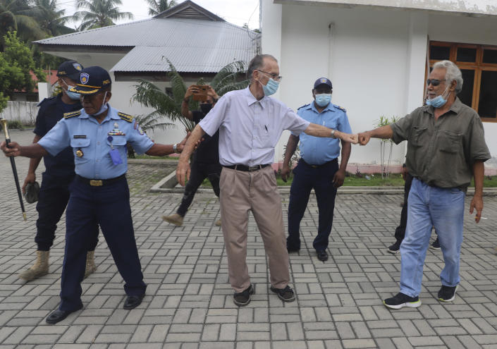 Xanana Gusmao, right, former East Timorese president and prime minister, gives a fist bump to Richard Daschbach, center, a defrocked priest originally from Pennsylvania accused of child abuse, after a hearing at a courthouse in Oecusse, East Timor, on Tuesday, Feb. 23, 2021. While he has his critics, Daschbach's support appears deep and widespread, extending beyond Oecusse to the capital, Dili. It includes members of the political elite, including Gusmao _ also an independence hero. (AP Photo/Raimundos Oki)