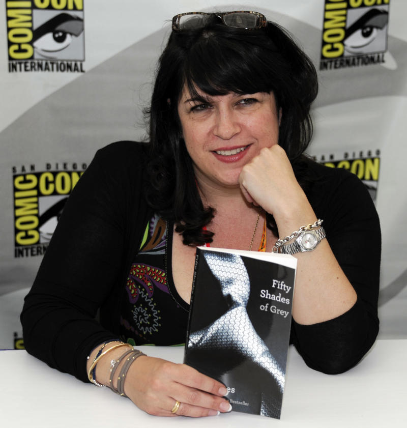 """FILE - This July 12, 2012 file photo shows author EL James posing with her book """"Fifty Shades of Grey"""" at a book signing during the first day of Comic-Con convention held at the San Diego Convention Center in San Diego. James will soon make her first visits to two hotspots featured in her erotic trilogy: Seattle and Portland.  Vintage Books announced Thursday that the Britain-based writer is including the two U.S. Pacific Northwest cities on a tour this fall to promote her multimillion-selling novels. James will appear at Seattle's Third Place Books on Sept. 22 and at Portland's Powell's Books on Sept. 24.   (Photo by Denis Poroy/Invision/AP, file )"""