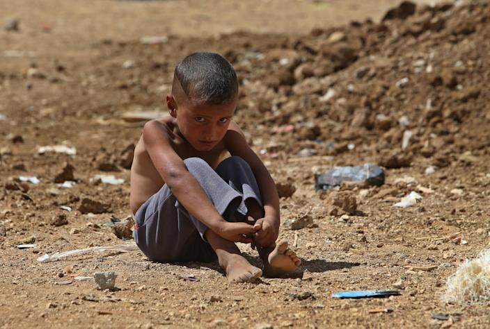 In this Wednesday, Sept. 11, 2013 file photo, A Syrian refugee boy sits on the ground at a temporary refugee camp, in the eastern Lebanese Town of Al-Faour, Bekaa valley near the border with Syria, Lebanon. With some 1 million Syrian refugees in Lebanon, or nearly 25 percent of the tiny Arab country's population, the guests from Lebanon's eastern neighbor are facing different kinds of racist behaviors by Lebanese. (AP Photo/Hussein Malla, File)