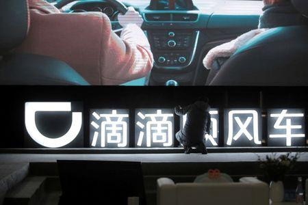 FILE PHOTO: Man is seen in front of a Didi sign before a promotional event of its Hitch service for the Spring festival travel rush, in Beijing
