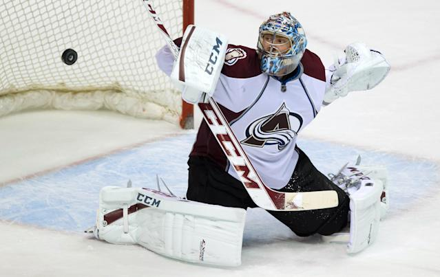 Colorado Avalanche goalie Semyon Varlamov, of Russia, makes a blocker save against the Vancouver Canucks during the third period of an NHL hockey game Thursday, April 10, 2014, in Vancouver, British Columbia. (AP Photo/The Canadian Press, Darryl Dyck)