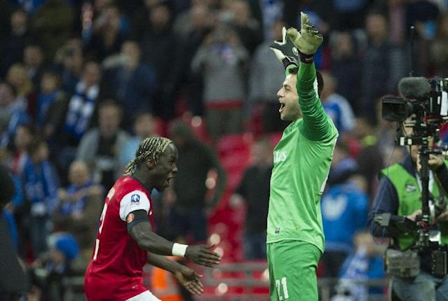Arsenal's Wojciech Szczesny, right, and Bacary Sagna, left, celebrate after winning against Wigan Athletic, during their English FA Cup semifinal soccer match, at the Wembley Stadium in London, Saturday, April 12, 2014. (AP Photo/Bogdan Maran)