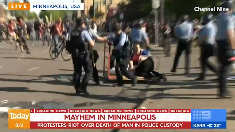 Police officers on the scene of protests in Minneapolis, US.