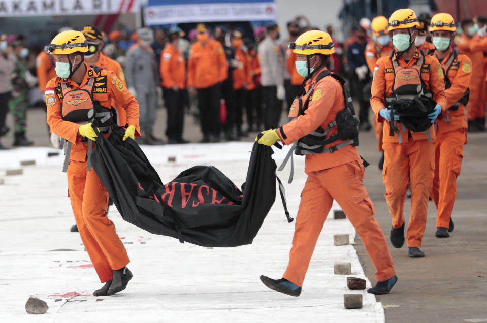 Rescuers carry body bags containing human remains retrieved from from the Java Sea where Sriwijaya Air flight SJ-182 crashed on Saturday, at Tanjung Priok Port in Jakarta, Indonesia, Thursday, Jan. 14, 2021. An aerial search for victims and wreckage of a crashed Indonesian plane expanded Thursday as divers continued combing the debris-littered seabed looking for the cockpit voice recorder from the lost Sriwijaya Air jet. (AP Photo/Dita Alangkara)