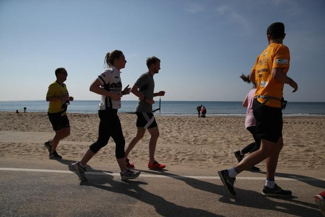 Joggers run along sea front