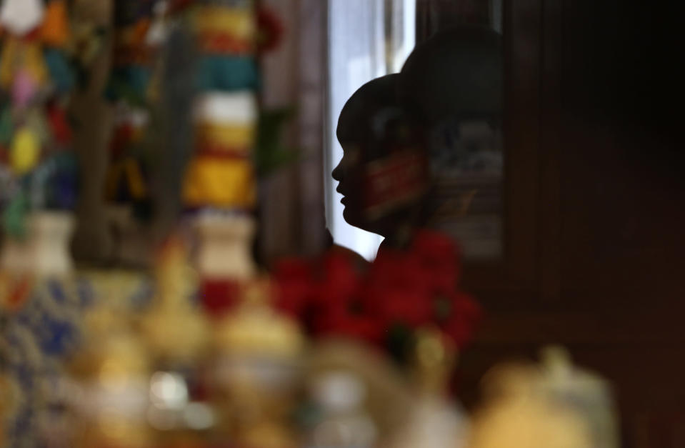 Jalue Dorje is reflected in the mirror of a shrine while reciting prayers during a ceremony on Monday, July 19, 2021, in Columbia Heights, Minn., paying homage to Guru Rinpoche, the Indian Buddhist master who brought Tantric Buddhism to Tibet. When he was an infant, Jalue, now 14, was identified as the eighth reincarnation of the lama Terchen Taksham Rinpoche. After finishing high school in 2025, Jalue will head to northern India and join the Mindrolling Monastery, more than 7,200 miles (11,500 kilometers) from his home. (AP Photo/Jessie Wardarski)