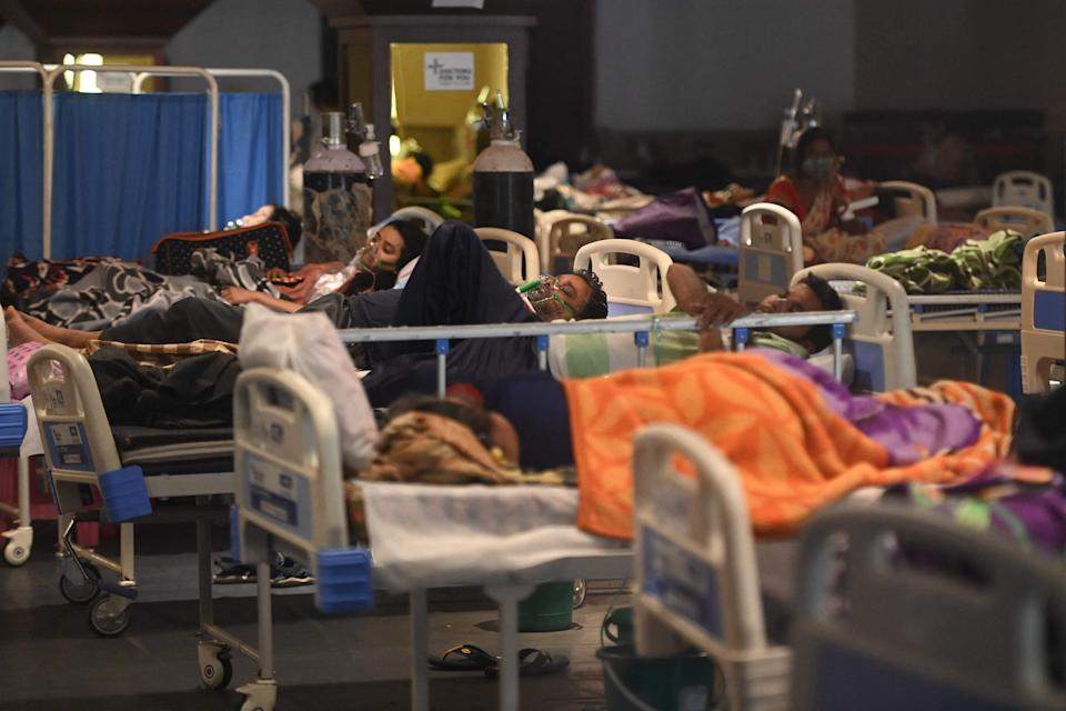 <p>Patients breath with the help of oxygen masks inside a banquet hall temporarily converted into a Covid-19 ward in New Delhi</p> (AFP via Getty Images)