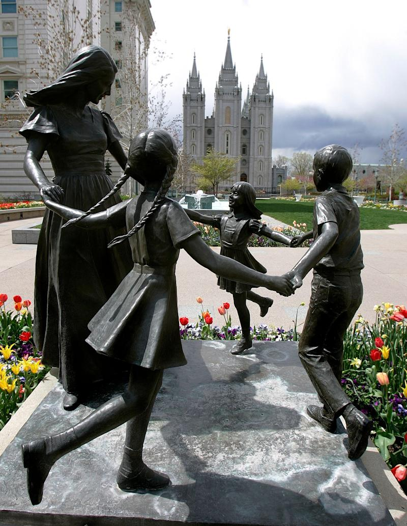 FILE - In this April 20, 2005 file photo, a statue by Dennis Smith representing womanhood with children stands in view of the Mormon Temple, rear, in Salt Lake City. The Church of Jesus Christ of Latter-day Saints has struggled for acceptance ever since its founder, Joseph Smith, said in the 19th century that God told him to restore the true Christian church by revising parts of the Bible and adding the Book of Mormon as a sacred text. (AP Photo/Douglas C. Pizac, File)