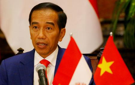 FILE PHOTO: Indonesian President Joko Widodo reads his statement following a signing ceremony at the Presidential Palace in Hanoi