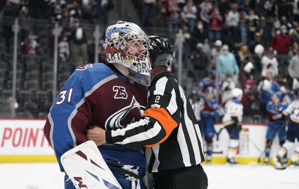 Referee Mike Hasenfratz, right, holds back Colorado Avalanche goaltender Philipp Grubauer as he exchanges words with St. Louis Blues goaltender Jordan Binnington after he skated down the ice to face Grubauer while he tangled with St. Louis Blues left wing Kyle Clifford as time ran out in Game 1 of an NHL hockey Stanley Cup first-round playoff series Monday, May 17, 2021, in Denver. Colorado won 4-1. (AP Photo/David Zalubowski)