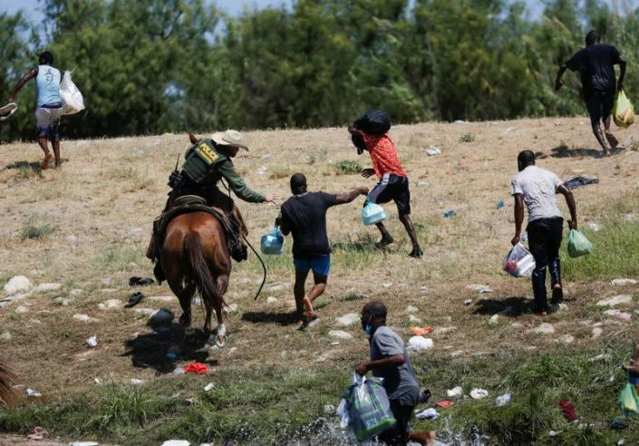 Migrants collecting food try to evade law enforcement at the U.S.-Mexico border