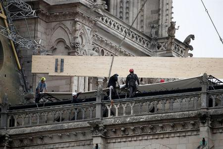 Workers install temporary tarpaulins to protect Notre-Dame Cathedral from rain damage, a week after a massive fire devastated large parts of the gothic structure in Paris