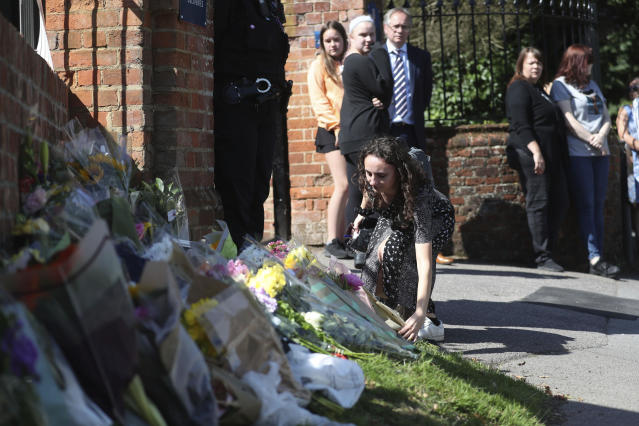 Flowers are placed at the entrance to The Holt School in Wokingham in memory of teacher James Furlong, a victim of a terror attack in nearby Reading. (PA)