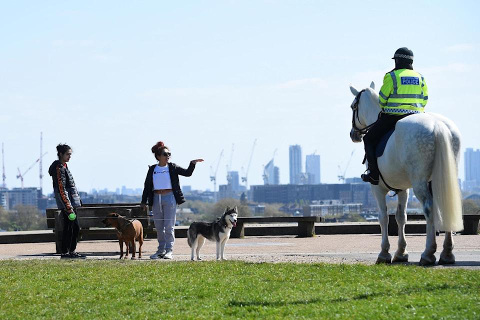 <p>Mounted police officers speak to people on Primrose Hill, London</p> (PA)