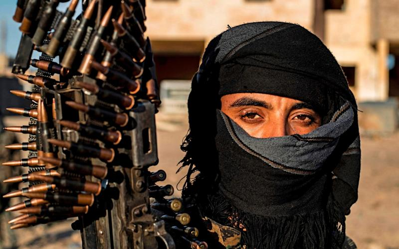 A fighter with the Syrian Democratic Forces in the town of Baghouz - AFP
