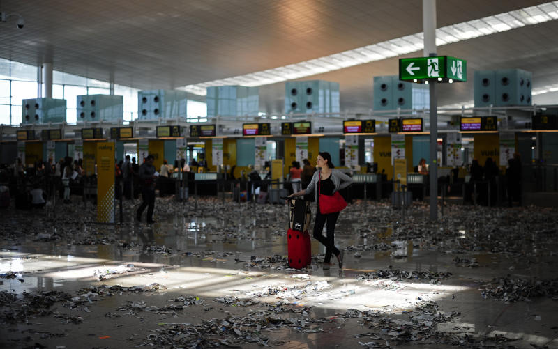 A passenger is seen among rubbish and paper during the second day of a strike by the cleaning staff against budget cuts at Barcelona's airport in Barcelona, Spain, Wednesday, May 30, 2012. The cleaners have put torn paper onto the floor as part of the action. (AP Photo/Manu Fernandez)