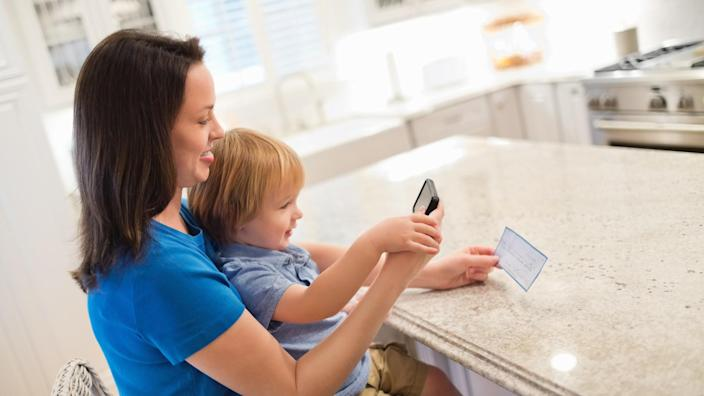 Side view of mother and son depositing check through smart phone in kitchen.