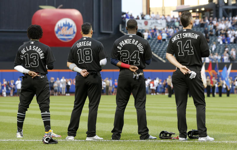NEW YORK, NEW YORK - AUGUST 23: Ronald Acuna Jr. #13, Rafael Ortega #18, Adeiny Hechavarria #24 and Matt Joyce #14 of the Atlanta Braves stand during the national anthem prior to a game against the New York Mets at Citi Field on August 23, 2019 in New York City. Teams are wearing special color schemed uniforms with players choosing nicknames to display for Players' Weekend. (Photo by Jim McIsaac/Getty Images)