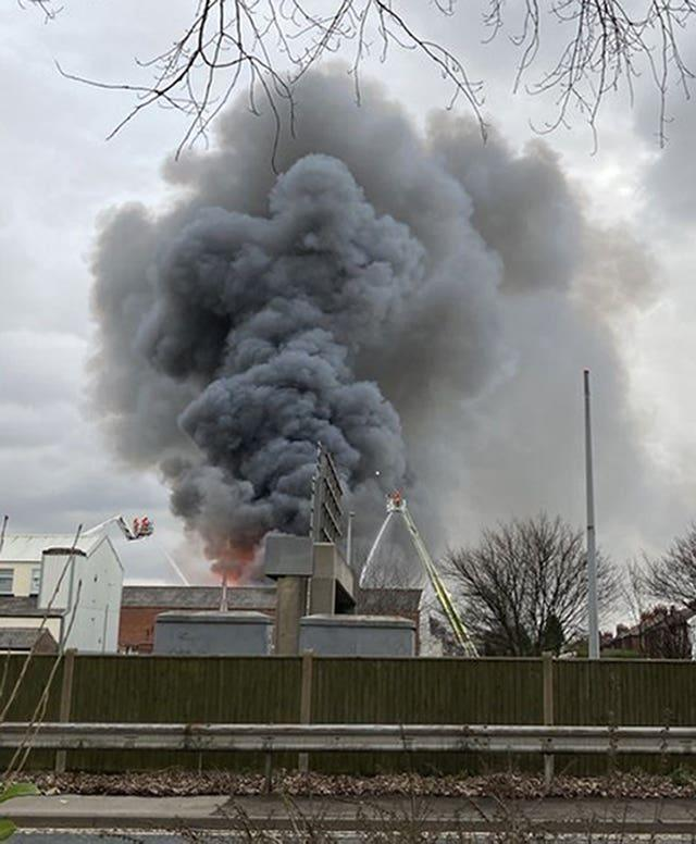 Smoke rises from a fire at a three-storey warehouse in Holland Street, Denton