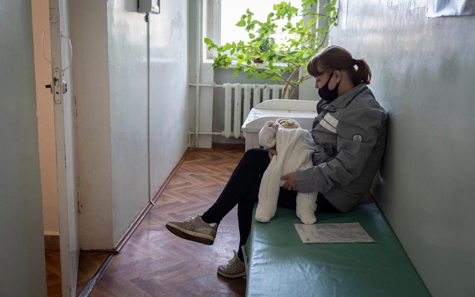 A woman waits with her baby in the waiting room of a doctor's surgery - Andrey Borodulin