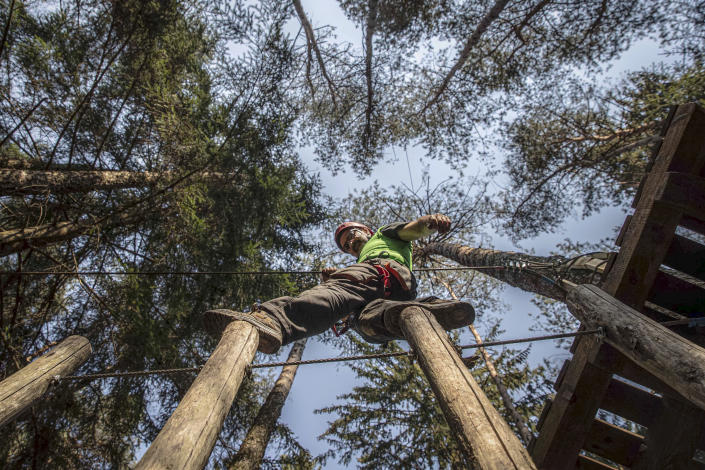 """In this image take on Thursday, April 23, 2020, Diego Fregona, 58, adventure park owner, balances on poles part of a trail in his park, in Clusone, near Bergamo, northern Italy. Fregona spent all his savings to repair the damage done to his 10.000sqm park after a whirlwind in October knocked down trees, climbing ropes and suspended trails, only to remain closed with very little money and lots of doubts as to whether he'll ever be able to restart. His words for the Associated Press were """"There isn't a family who didn't have a bereavement, the only thing left to do is to get up again."""" (AP Photo/Luca Bruno)"""
