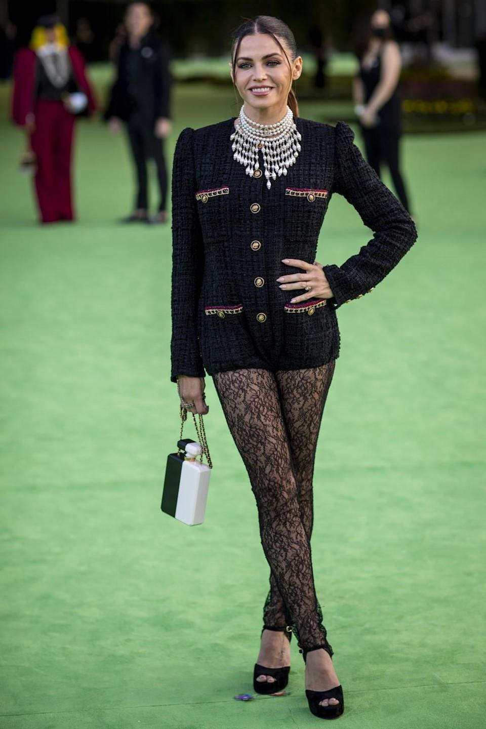 A woman in a black, button-down jacket and lace pants posing on a green carpet
