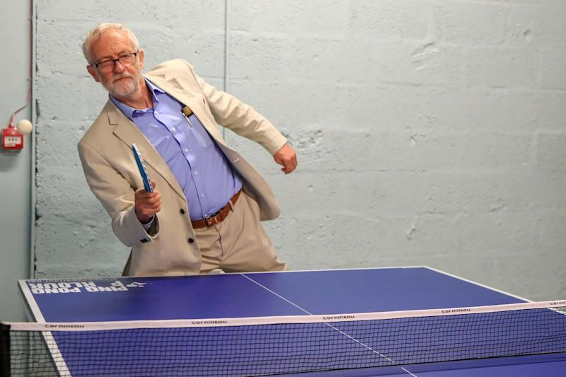Mr Corbyn tries table tennis during a visit to a converted empty shop unit (PA)