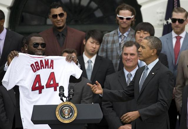 "President Barack Obama is given a Boston Red Sox jersey from Boston Red Sox designated hitter David ""Big Papi"" Ortiz during a ceremony on the South Lawn of the White House in Washington, Tuesday, April 1, 2014, to honor the 2013 World Series baseball champion Boston Red Sox. In the background are pitcher Junichi Tazawa, second row left, manger John Farrell, Koji Uehara, second row right. (AP Photo/Carolyn Kaster)"